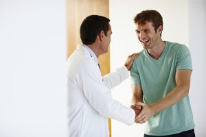 Portrait of happy young patient shaking hands with successful doctor